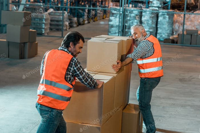 warehouse workers in vests moving boxes in storehouse