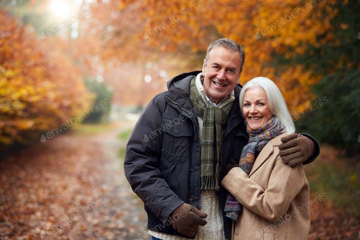 Portrait Of Loving Senior Couple Hugging As They Walk Along Autumn Woodland Path Through Trees