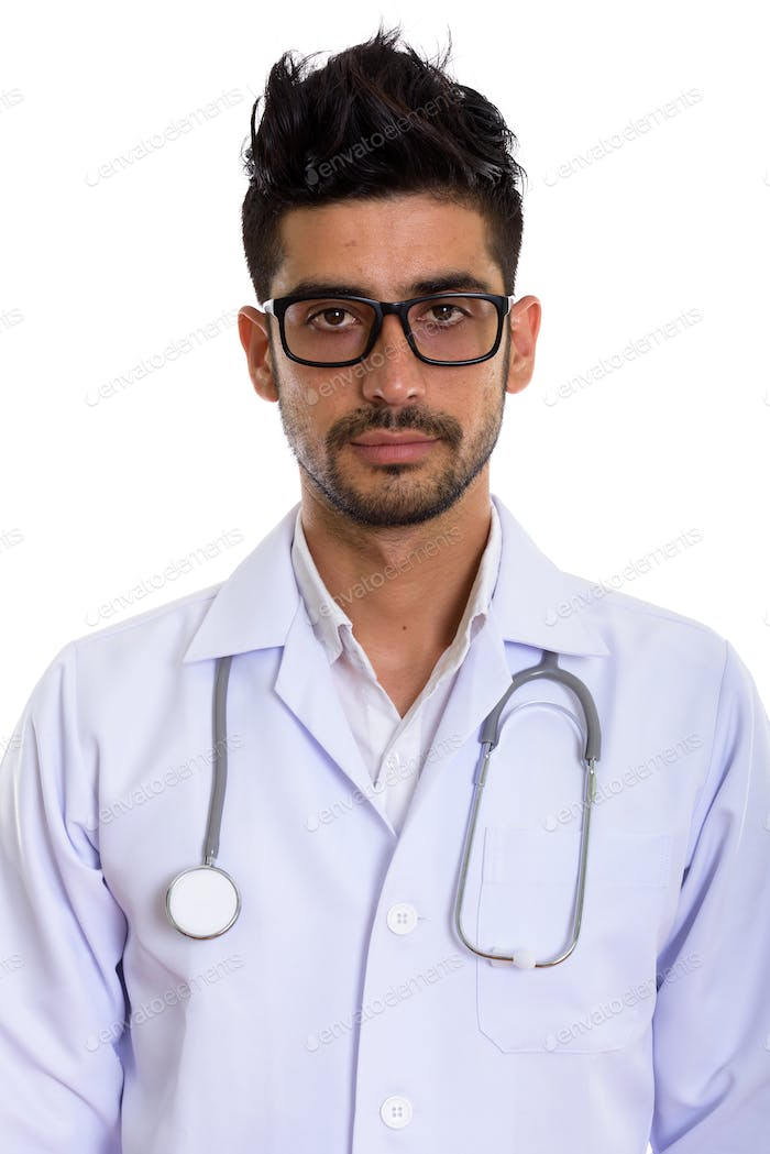 Young handsome bearded Persian man doctor with eyeglasses