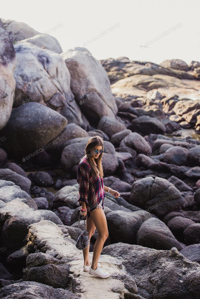 Stylish hipster woman in checkered shirt and shirts on summer beach at sunset. Path in a rocks at