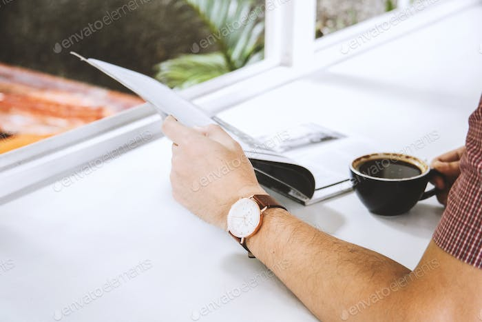 Man hand holding a magazine and a cup of coffee