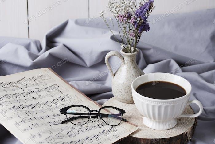 Schwarzer Kaffee und Musiknote auf dem Bett