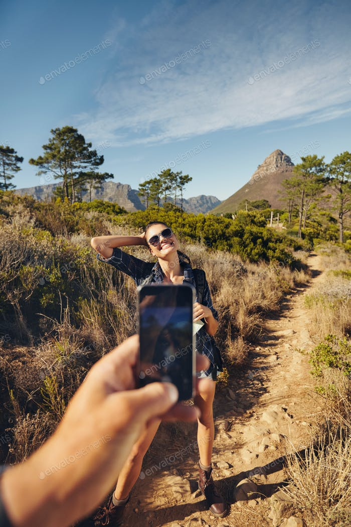 Woman posing for picture while hiking