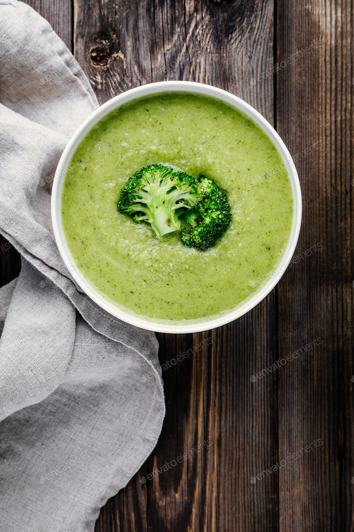 Homemade broccoli cream soup in white bowl with toasts on wooden background