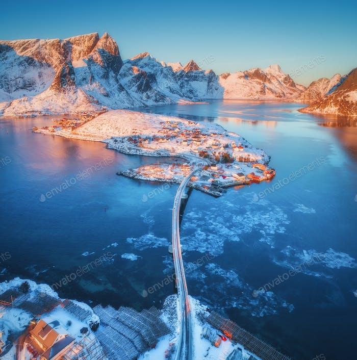 Luftaufnahme der Brücke über das Meer und die verschneiten Berge in Norwegen