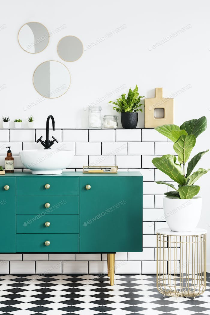 Green cabinet next to plant on gold table in modern bathroom int