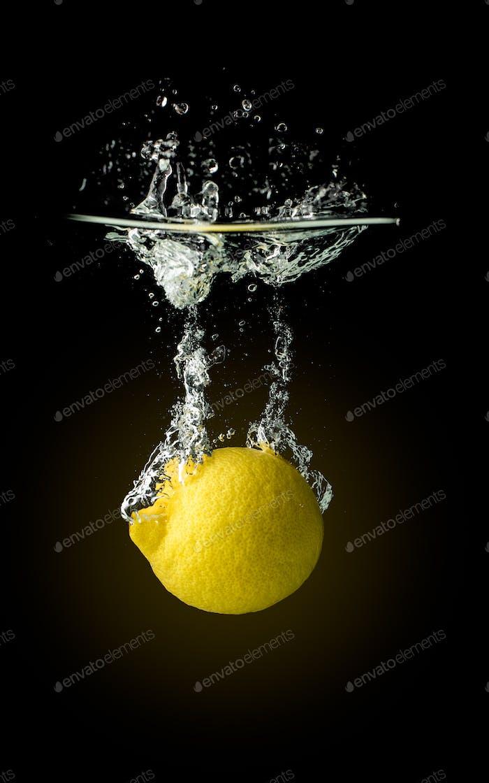Lemon fruit splashing into water and sinking Isolated on black background