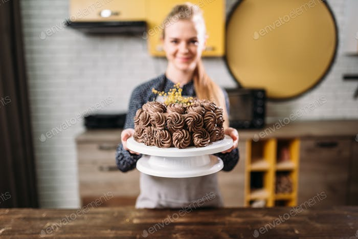 Woman shows chocolate cake, culinary masterpiece
