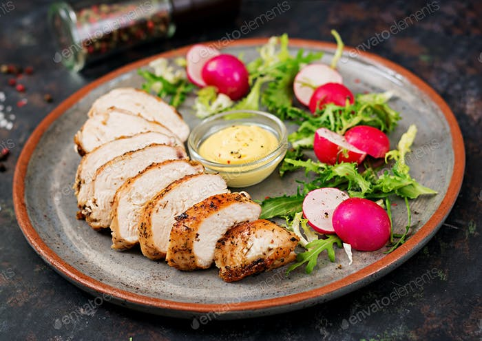 Baked chicken breast and fresh vegetables on the plate on a dark background.
