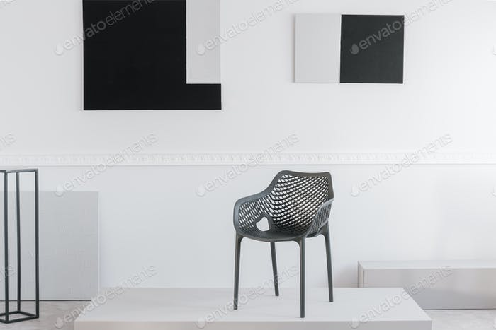 Fashionable grey metal chair on white platform in fancy showroom