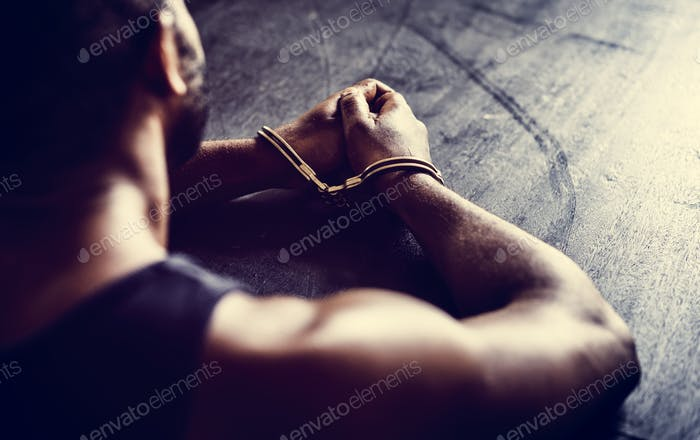 Guy with handcuffs sitting at a table
