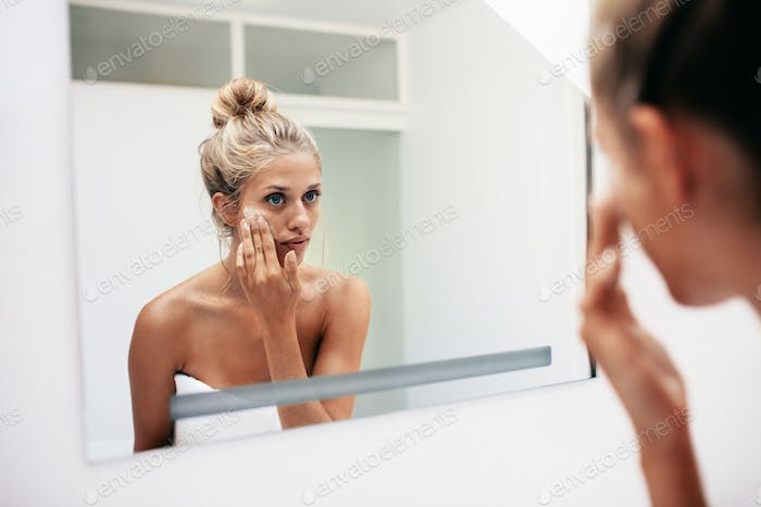 Female putting on moisturizer on her facial skin