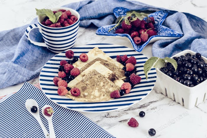 pancakes with raspberry, currant on blue stripped plate with textile, close-up white marble