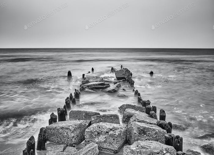 Black and white picture of an old breakwater on a beach.