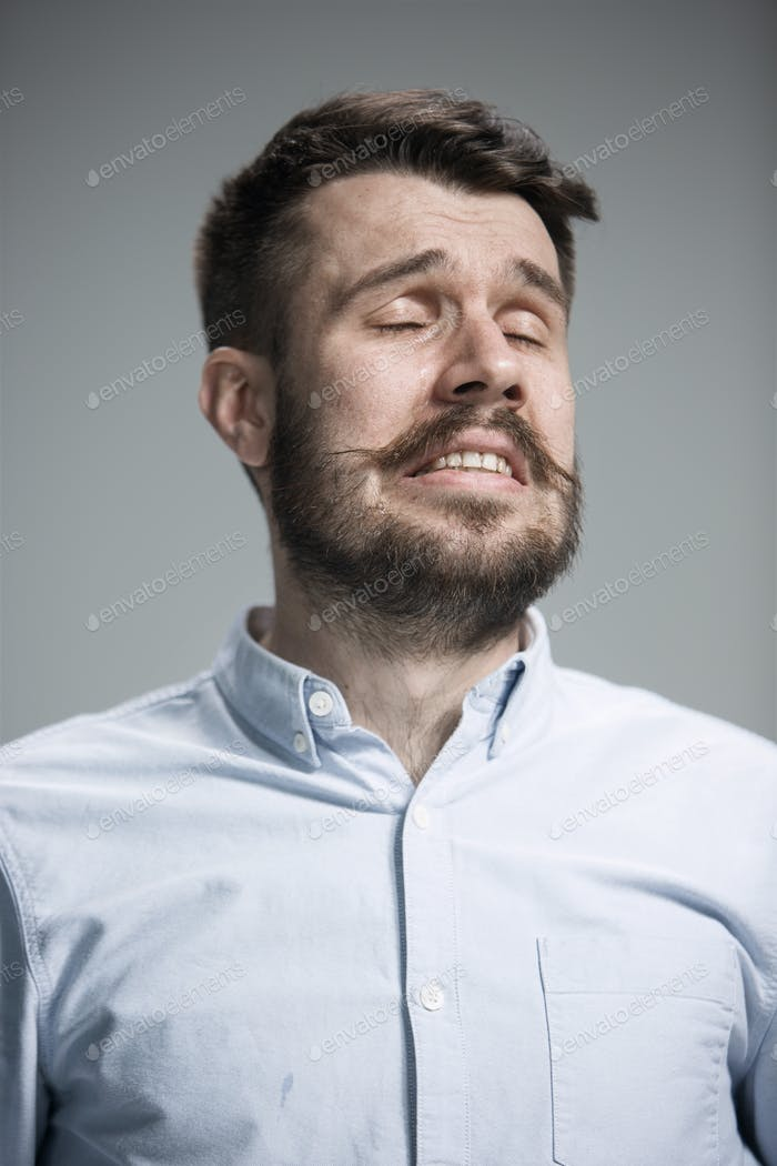 The crying man with tears on face closeup