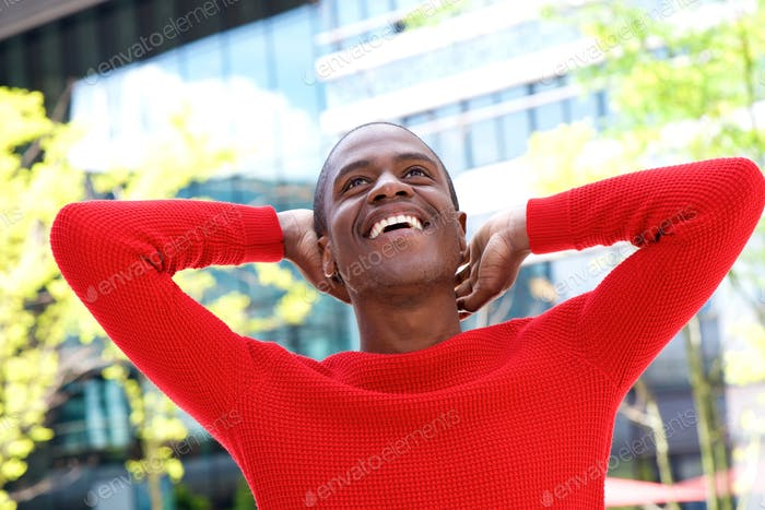 African american man laughing with hands behind head