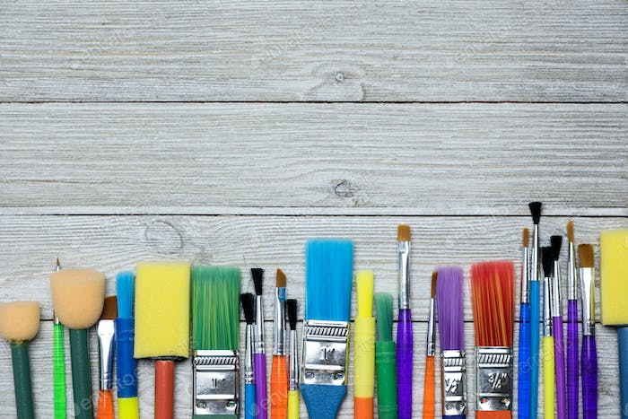 Row of artist paint brushes on old wooden background