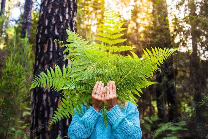 Portrait of unrecognizable people hidden by big leafs