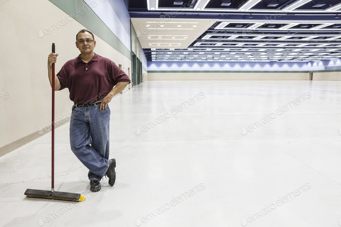 An hispanic workman standing in a large interior space with a broom.