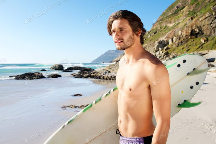 Handsome man standing with surfboard by the ocean