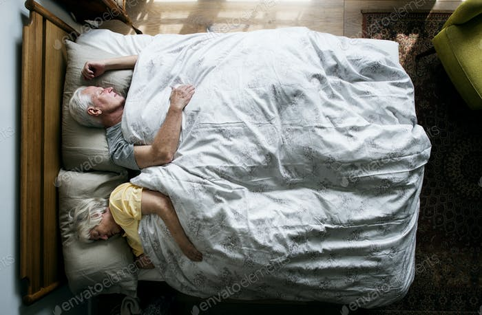 Elderly Caucasian couple sleeping on the bed