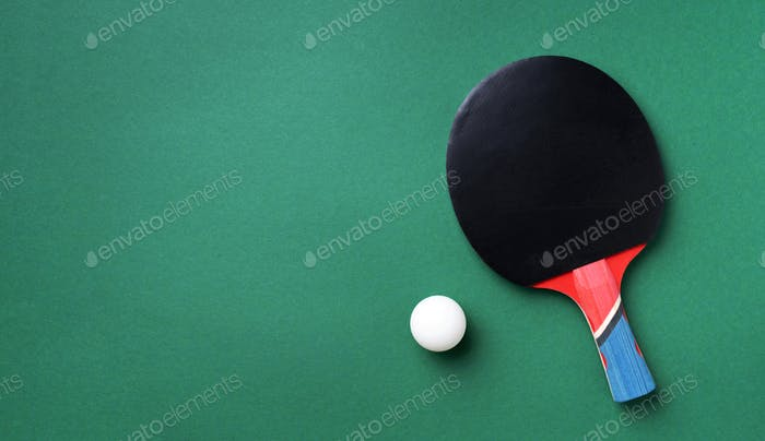 Table tennis rackets and white ball on green background with copy space. Top view. Flat lay. Sport