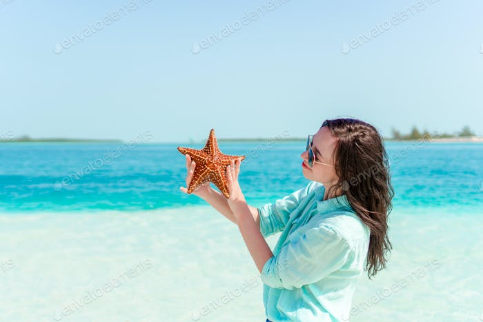 Adorable girl with starfish on the beach