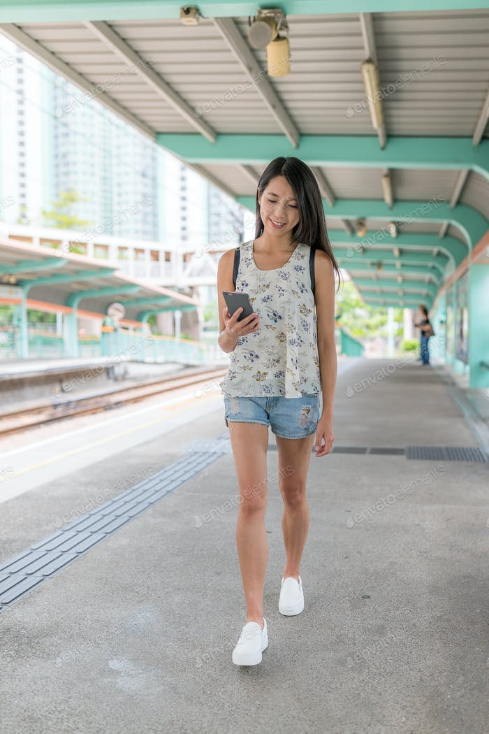 Woman using mobile phone in light rail station of Hong Kong