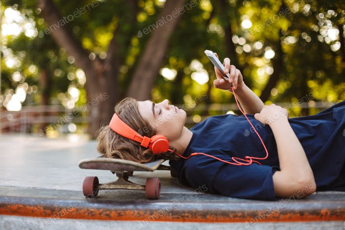 Thumbnail for Young guy in orange headphones lying on skateboard while dreamil