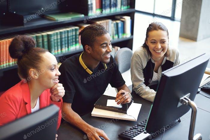 Studenten, die am Computer in einer College-Bibliothek arbeiten