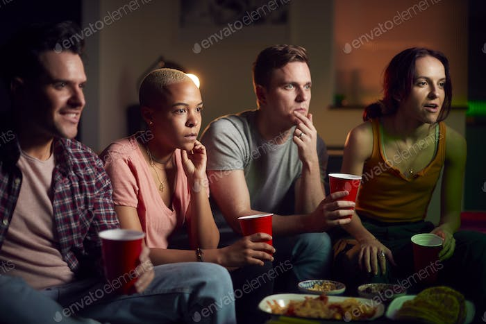 Group Of Friends With Drinks Sitting On Sofa At Home Watching Horror Movie Together