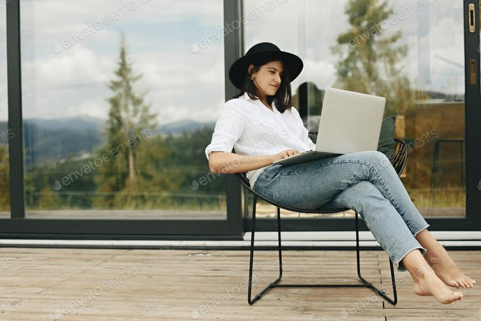 Stylish hipster girl sitting with laptop on terrace at big window.