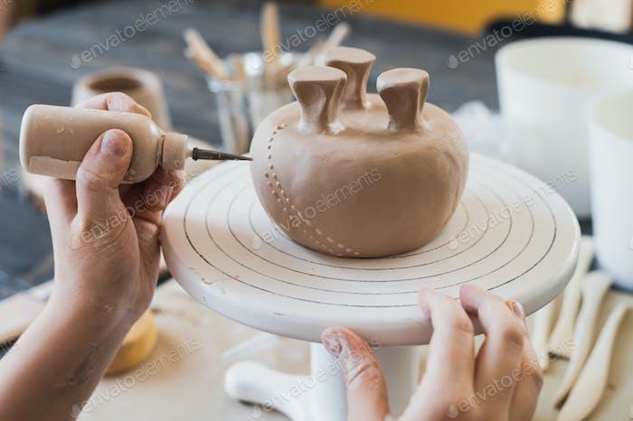 Kind in den Prozess der Dekoration der Tonvase. Kinder Töpferei Studio