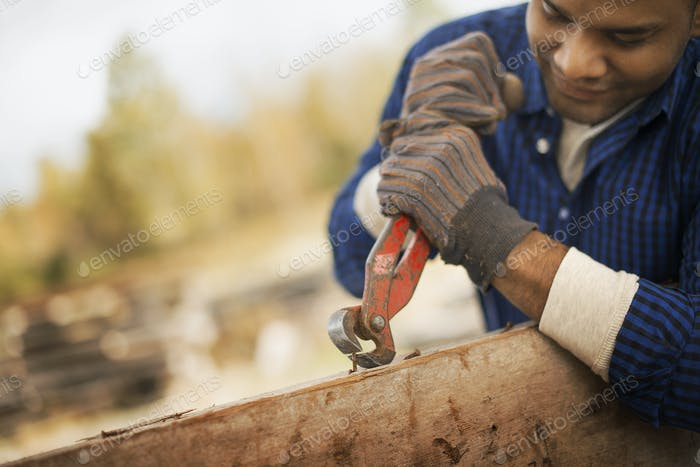 A man working in a reclaimed timber yard, removing metal from a piece of timber.