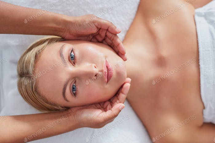 Beautiful woman having a face massage at health spa
