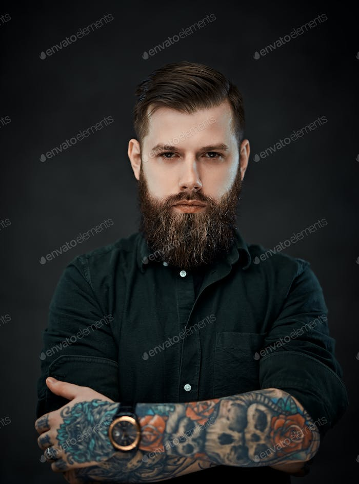 Handsome tattooed man with stylish haircut posing on a dark background