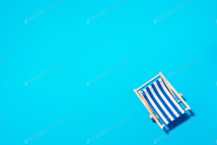 Flat lay of beach deck chair on blue background with copy space. Summer and travel concept. Creative