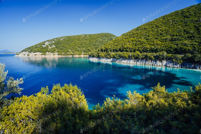 Stunning seaside scenery of the cove with turquoise calm sea water, surrounded by hills overgrown
