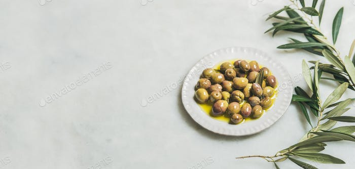 Pickled green Mediterranean olives and olive-tree branch, wide format