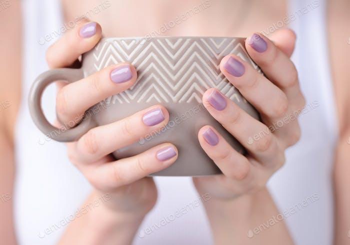Hände einer jungen Frau halten eine Tasse Tee