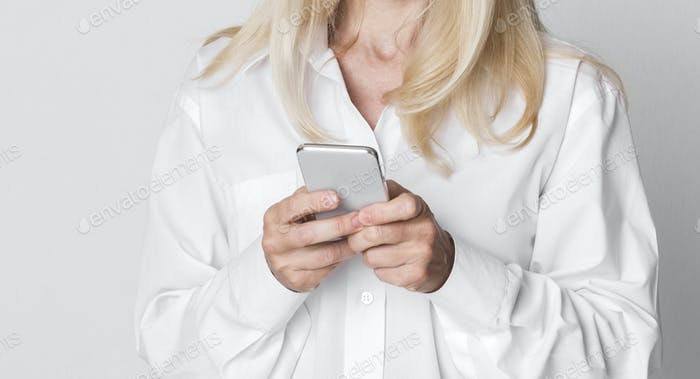 Mature Businesswoman Texting On Cellphone At Studio