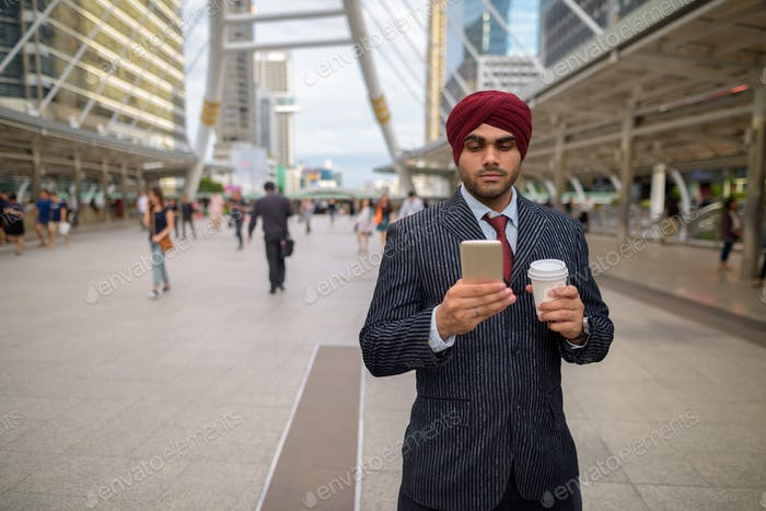 Indian businessman outdoors in city using mobile phone
