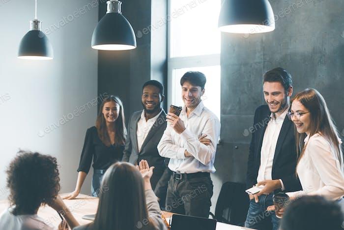 Business people having break and talking at meeting