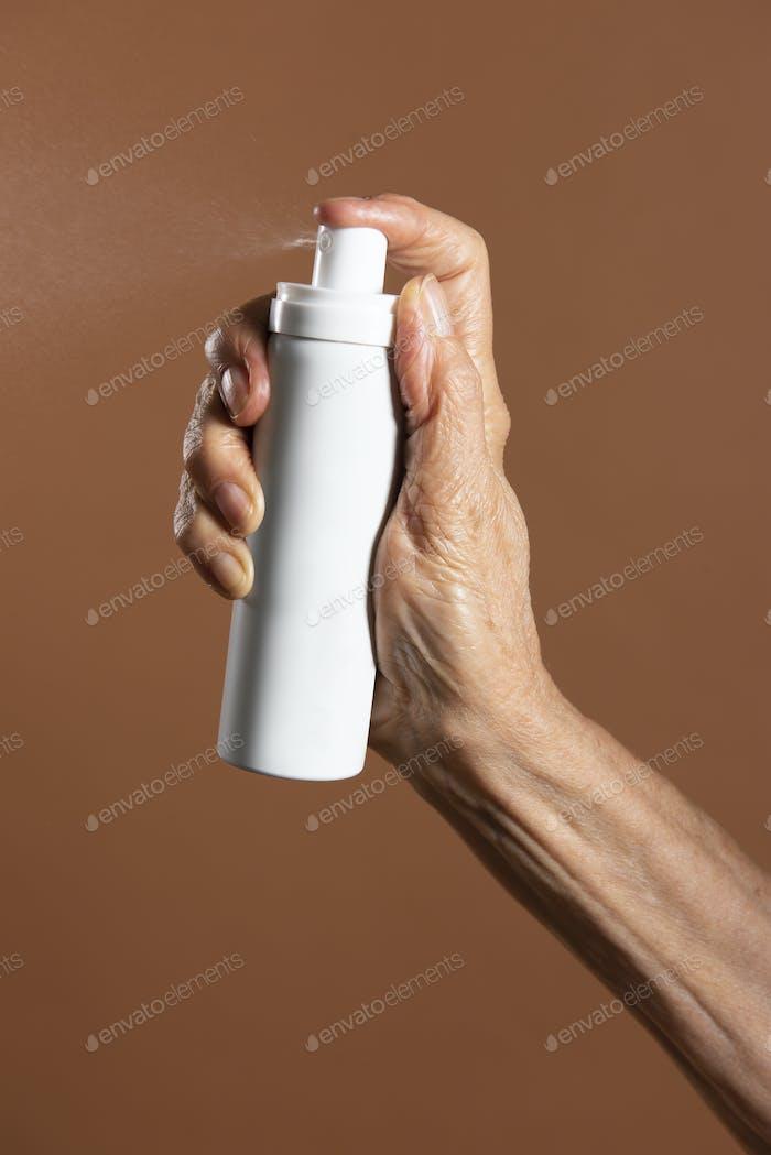 Hand holding a white aerosol spray bottle