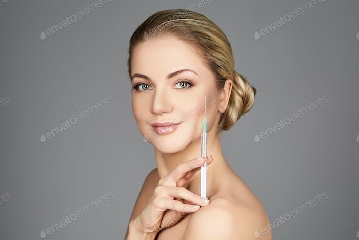 beautiful girl holding syringe