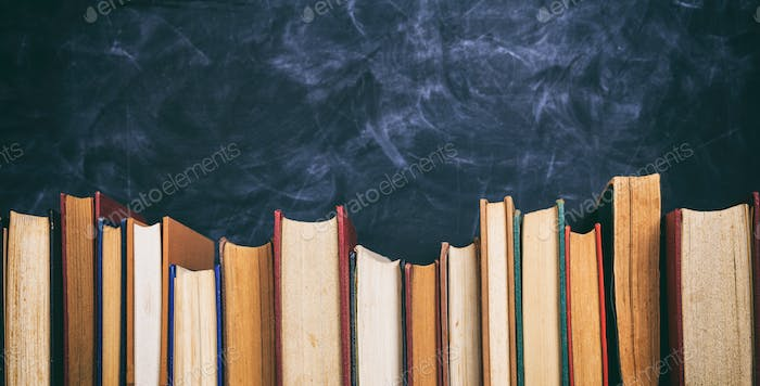 Vintage books on blackboard background- copy space