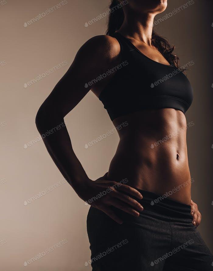 Muscular young woman posing in sportswear