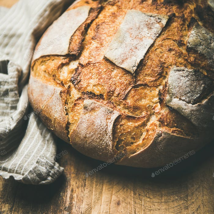 Sourdough wheat bread over rustic background, square crop