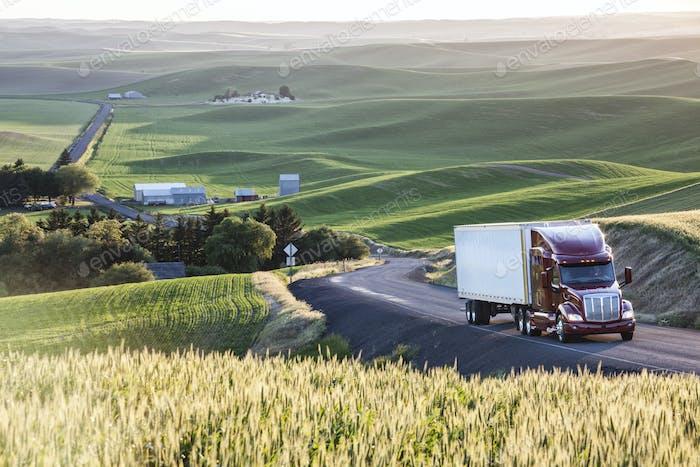 kommerziell LKW fahren durch Weizenfelder im Osten von Washington, USA bei Sonnenuntergang.