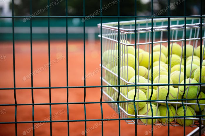 Tennis balls in basket on background of the tennis court